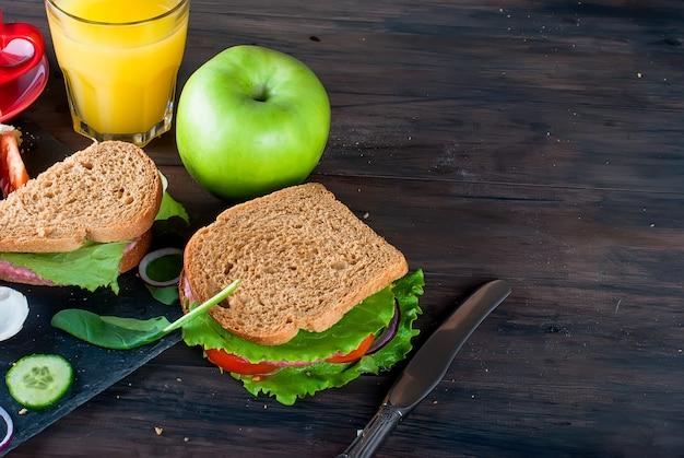 Sándwich, huevo, taza de café y vaso de jugo para el desayuno.
