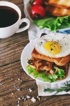 Sandwich con huevos, pollo, pepino y lechuga sobre un fondo de madera copia espacio