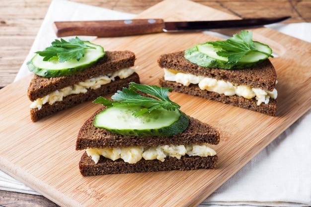 Sandwich con huevos revueltos y pepinos sobre fondo rústico de madera