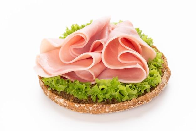 Sándwich de jamón de cerdo sobre fondo blanco.