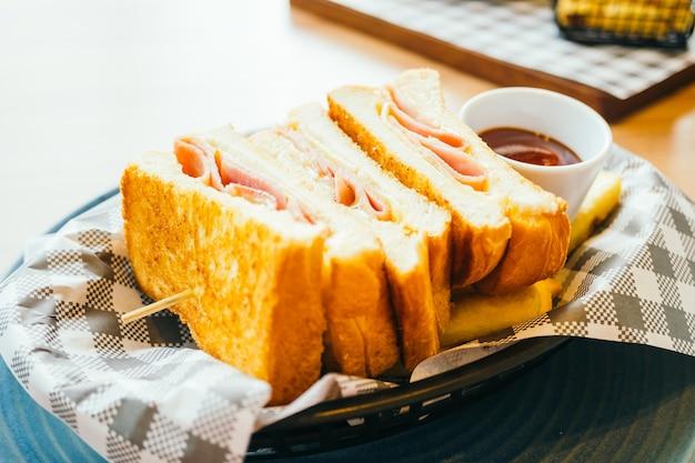 Sándwich de jamón con queso y papas fritas y salsa de tomate.