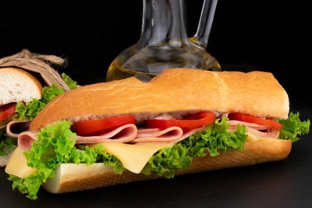 Sandwich con jamón, queso, tomate, lechuga sobre piedra.
