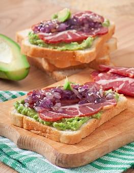 Sandwich con jamón, salsa de aguacate y cebolla caramelizada