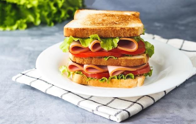 Sándwich con jamón de tomate lechuga en placa sobre fondo gris vista lateral