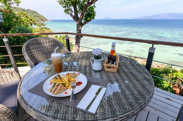 Sándwich de jamón con verduras, papas fritas y café helado en una mesa de madera en el patio con vista al mar