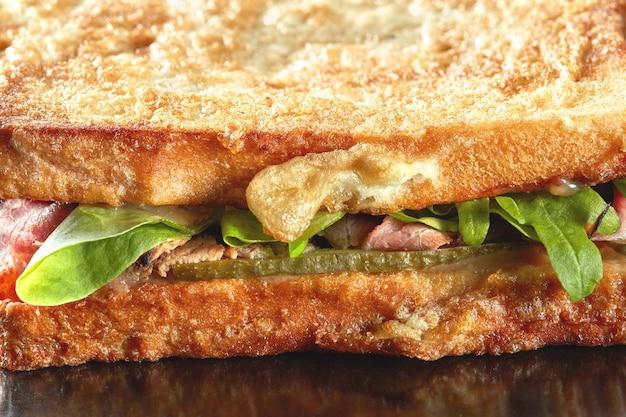 Sándwich de macro con pepino, ensalada, jamón y huevos en la placa negra