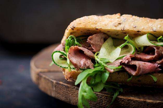 Sandwich de pan integral con rosbif, pepino y rúcula.