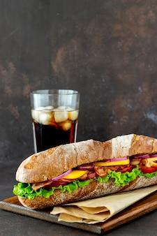 Sandwich de pan negro con ensalada, tocino, tomate, queso y cebolla. desayuno. comida rápida.