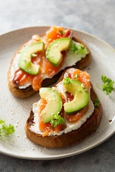 Sándwich de pan tostado de salmón pescado rojo y aguacate para el desayuno en un plato sobre fondo de mármol gris