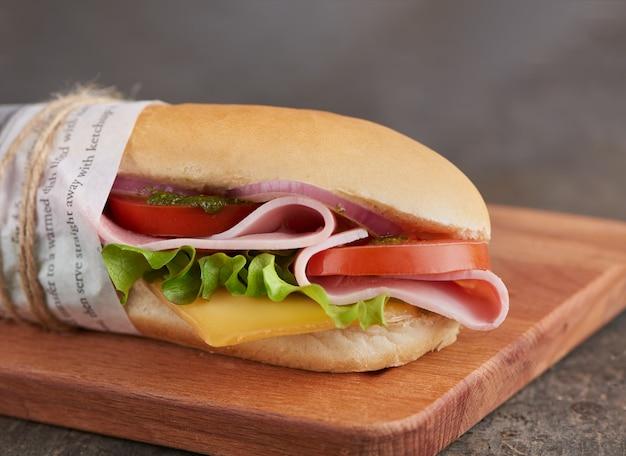 Sándwich de panini con jamón y queso con tomatios frescos y ensalada sobre tabla de madera.