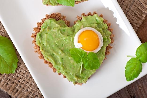 Sandwich con pasta de aguacate y huevo en forma de corazón
