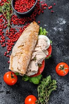 Sandwich con paté de hígado de bacalao, rúcula, tomate, huevo y hierbas.