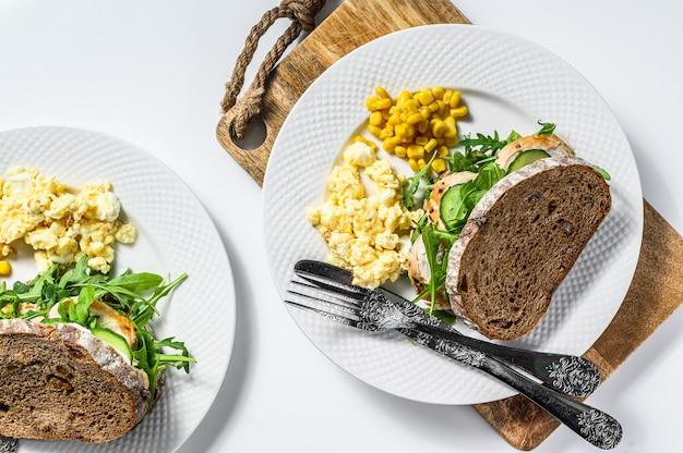 Sándwich de pavo con rúcula, cebolla y queso en pan integral. vista superior