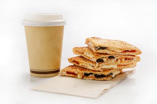 Sandwich con queso, aceitunas y una taza de papel con café.