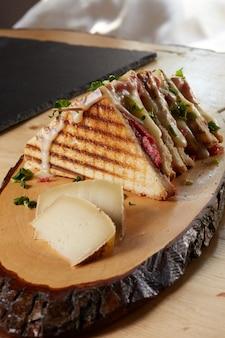 Sandwich y queso en una bandeja de madera