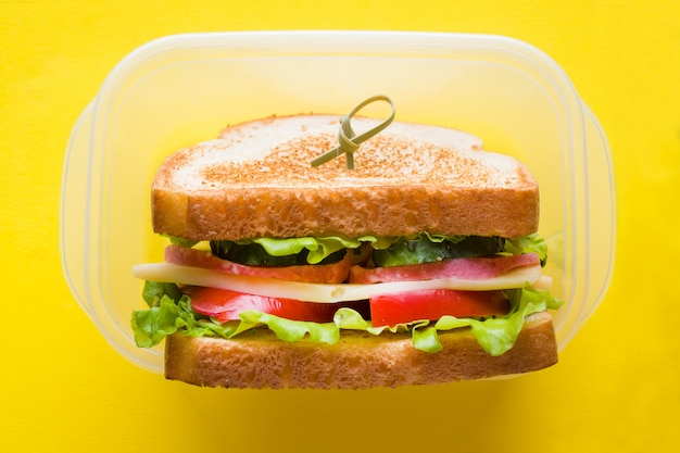 Sándwich con queso, jamón y verduras frescas en un recipiente en amarillo brillante