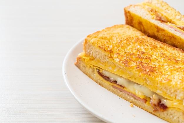 Sándwich de queso, tocino, jamón y tostadas francesas caseras con huevo
