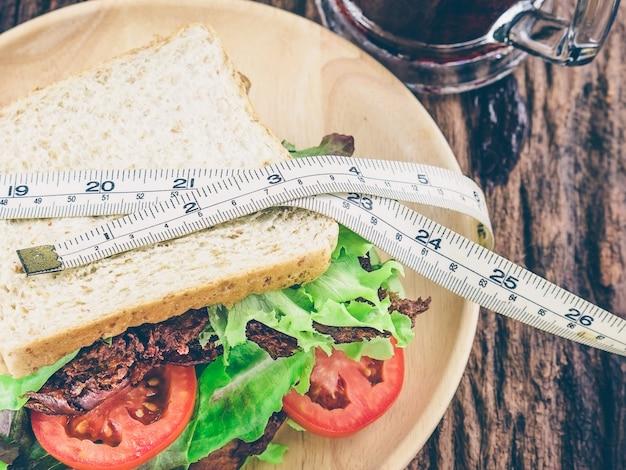 Sándwich con refresco frío y cinta métrica como concepto de dieta