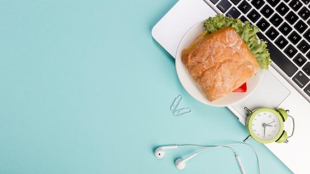 Sandwich, reloj despertador, auriculares en la computadora portátil contra el fondo azul