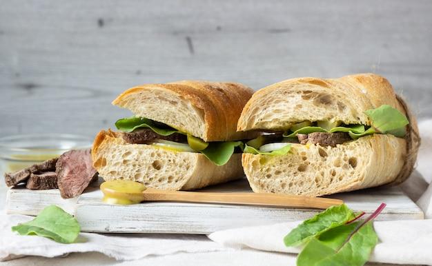 Sándwich de rosbif con ensalada, cebolla y cukes y salsa de mostaza.