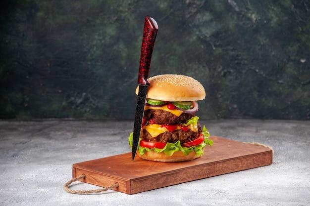 Sándwich sabroso casero y tenedor sobre tabla de cortar de madera en superficie borrosa