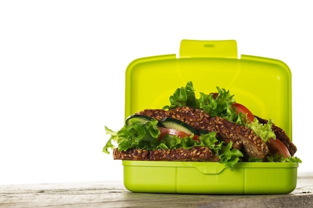 Sandwich sabroso vegetariano vegetariano vegetariano en la caja de almuerzo en la mesa de madera sobre fondo blanco aislado. horizontal. espacio de la copia.