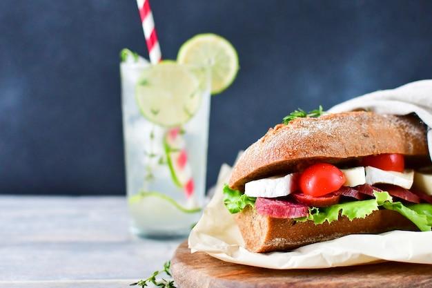 Sandwich con salami y queso en un plato de madera