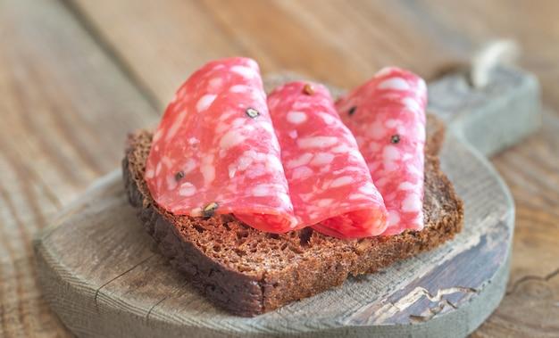 Sandwich con salami en el tablero de madera