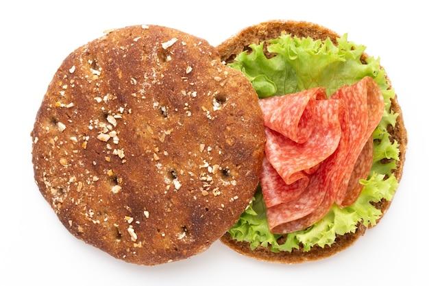 Sándwich con salchicha de jamón sobre fondo blanco.