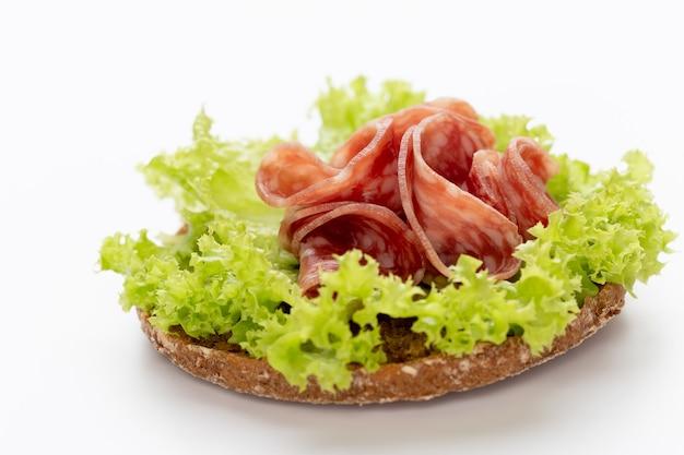 Sándwich con salchicha de salami sobre fondo blanco.