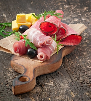 Sandwich con salchichas, aceitunas, tomate y rúcula sobre la madera vieja