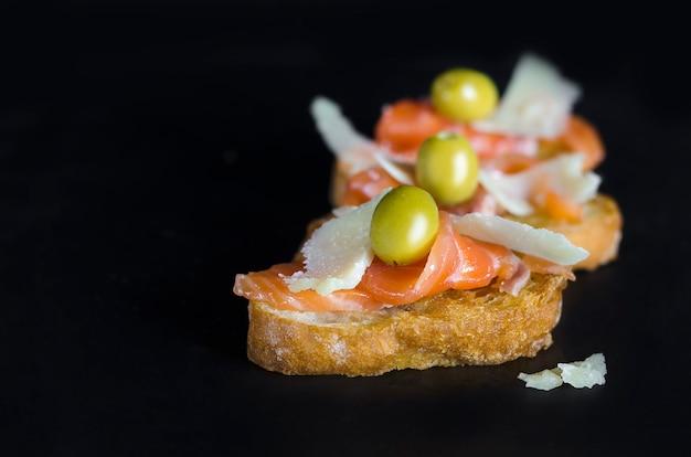 Un sándwich de salmón fresco con queso sobre fondo negro.