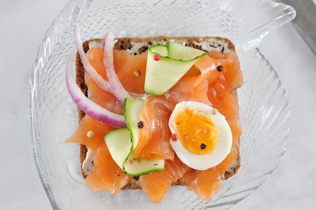 Sandwich con salmón, pepino, huevo y cebolla.