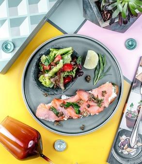 Sandwich con salmón y verduras en el plato