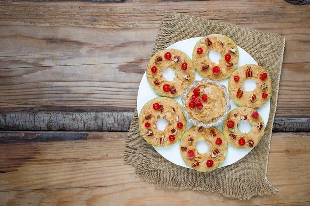 Sandwich saludable. rondas de manzana verde con mantequilla de maní y grosellas rojas y nueces pecanas en rústica, vista superior