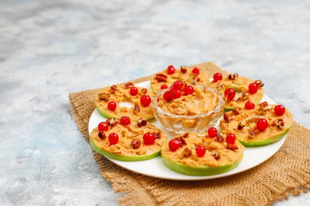 Sandwich saludable. rondas de manzana verde con mantequilla de maní y grosellas rojas y nueces pecanas sobre hormigón gris, vista superior