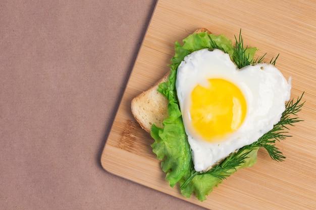 Sándwich de san valentín hecho con pan frito, huevo frito en forma de corazón y una hoja de lechuga