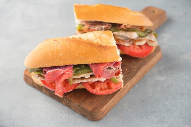 Sandwich serranito típico de andalucía con jamón, pimiento y lomo de cerdo a la plancha