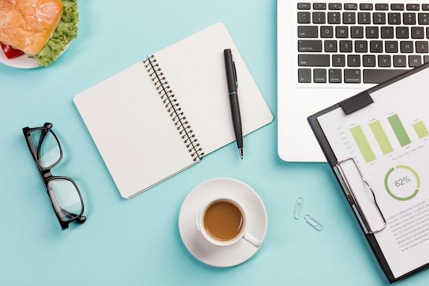 Sandwich, taza de café, lentes, bloc de notas en espiral, bolígrafo, computadora portátil y portapapeles con un plan de presupuesto en el escritorio azul