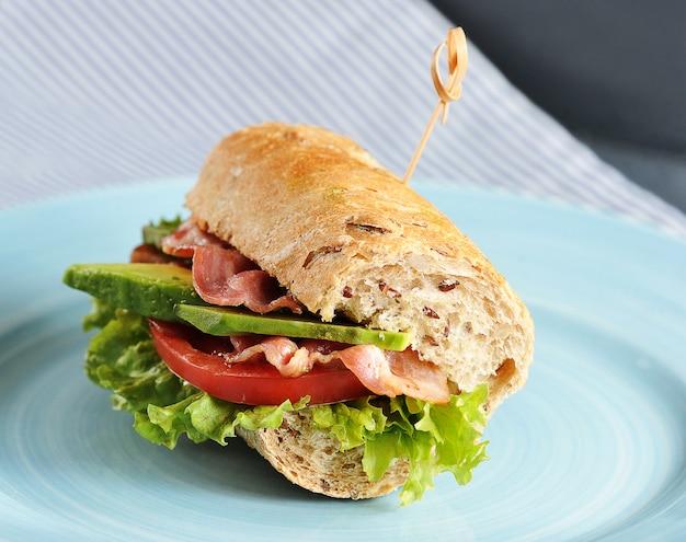 Sandwich con tocino y aguacate perforado con una brocheta