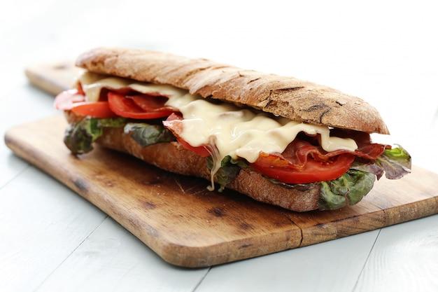 Sándwich de tocino y queso sobre tabla para cortar