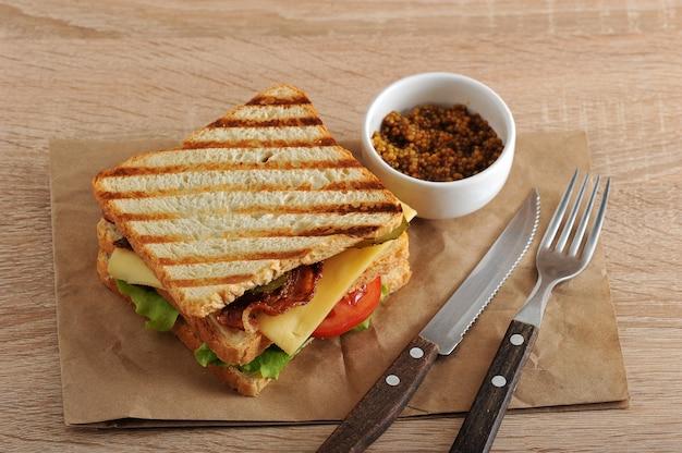 Sandwich con tocino, queso, tomate y mostaza dijon