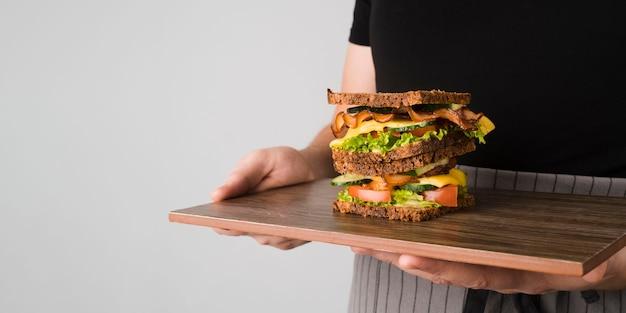 Sandwich con tocino sobre tabla de madera