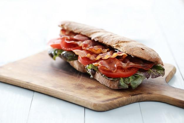 Sandwich de tocino en tabla de cortar de madera