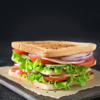 Sandwich con tocino, tomate, cebolla, ensalada.