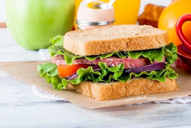 Sándwich con tocino y verduras sobre fondo blanco