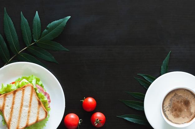 Sandwich; tomates y taza de café con hojas sobre fondo negro