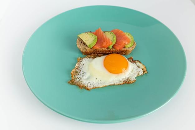 Sándwich de tostadas caseras con salmón y aguacate sobre una rebanada de pan de cereales. huevos fritos con yema brillante sobre un fondo de menta.