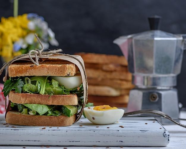 Sándwich de tostadas y hojas de lechuga y huevo cocido.