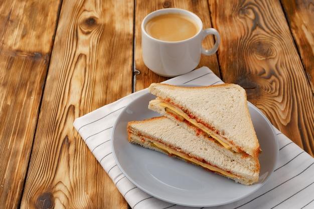 Sándwich de tostadas en plato y taza de café en una servilleta sobre mesa de madera